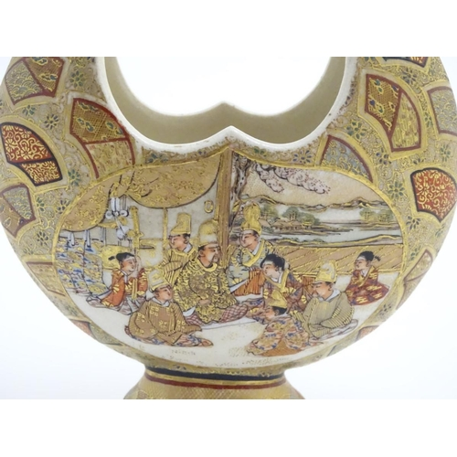 24 - A Japanese satsuma moon basket vase with hand painted decoration depicting figures seated around imp...