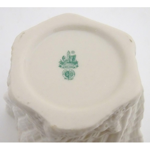 34 - Two Belleek Ireland pottery wares, comprising a twisted lustre shell vase / flower pot with a green ...