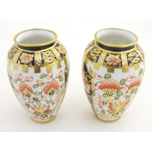 39 - Two small Crown Derby Imari vases, with floral decoration and gilt highlights. Marked under. Approx....