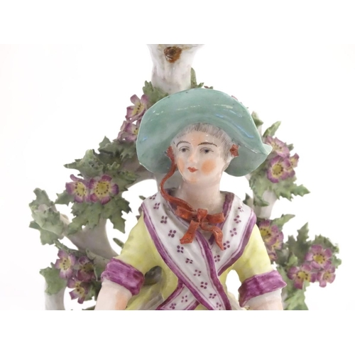 49 - A 19thC candlestick bocage figure, depicting a woman with a basket of flowers raised on a scrolling ...
