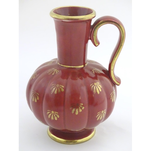 58 - A Swedish single handled vase with a ribbed bulbous body and an elongated neck, with gilt stylised f...