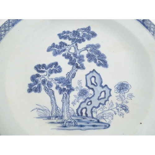 2 - A Chinese blue and white charger decorated with a stylised landscape with trees and flowers, and a p...