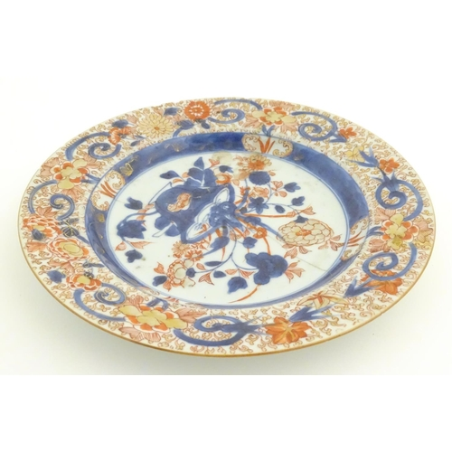 21 - A Japanese plate with floral decoration in the Imari palette. Approx. 8 3/4