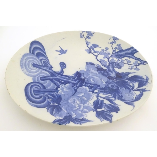 22 - A Chinese blue and white charger with stylised tree decoration, with cherry blossom and blooming flo...