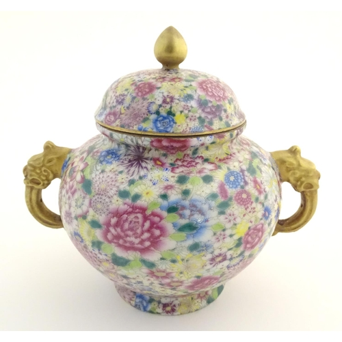 "A Chinese famille rose millefiore twin handled pot and cover decorated with a profusion of flowers and foliage. The handles of stylised animal form. Qianlong character marks under. Approx. 7"" high"