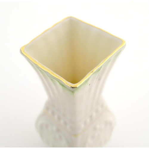 35 - A small Belleek bud vase of squared form with fluted neck and relief decoration. Approx. 4