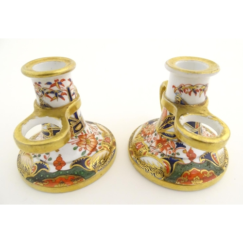 38 - A pair of Derby style chamber sticks in the Imari palette, with stylised flowers and scrolling folia...