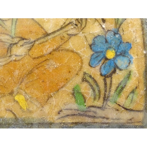 46 - A 19thC rectangular Persian tile with hand painted decoration depicting a seated man playing a music...