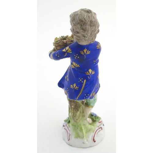 52 - A Dresden porcelain figure of a boy with a basket of flowers. Marked under. Approx. 5 1/4