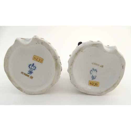 53 - A pair of German Sitzendorf porcelain florist figures, a gentleman and lady, each seated on a stylis...