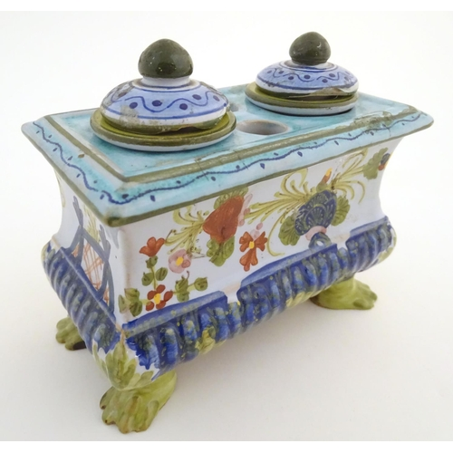54 - A Continental faience inkwell of sarcophagus form  on four paw feet with hand painted floral decorat...