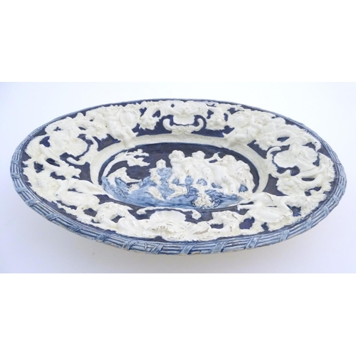 55 - An Italian style charger of oval form with relief decoration depicting putti in a landscape. The scr...
