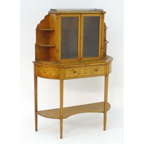 1015 - A 19thC satinwood cabinet with a pierced brass gallery above two glazed doors flanked by graduated s...