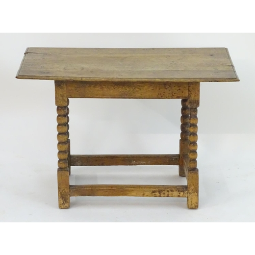 1024 - An 18thC oak occasional table with a planked top above bobbin turned supports terminating in block f...