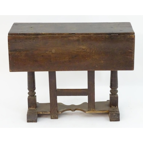 1025 - An early / mid 17thC oak gateleg table with a rectangular top above turned tapering supports and a s...