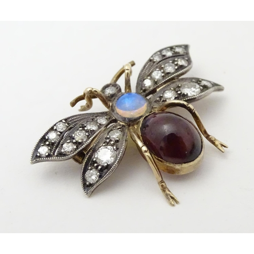 "A late 19thC / early 20thC brooch formed as a winged insect , with garnet cabochon and opal body and set with a profusion of diamonds. Unmarked. Tests as 18ct.  1 1/4"" wide"