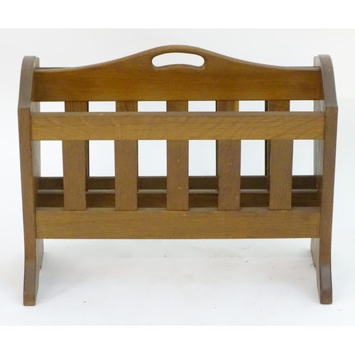 1049 - A mid 20thC oak Alan 'Acornman' Grainger magazine rack with shaped ends and slatted dividers with a ...
