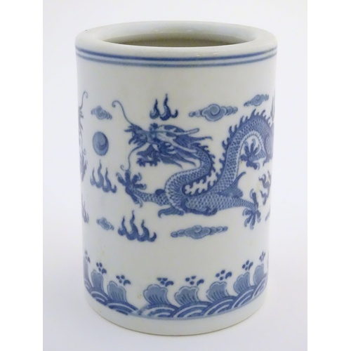 6 - A Chinese blue and white cylindrical brush pot decorated with stylised dragons, clouds and flames. C...