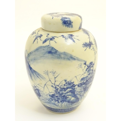 8 - A large blue and white Japanese lidded ginger jar decorated with a sage sat by a tree in a landscape...