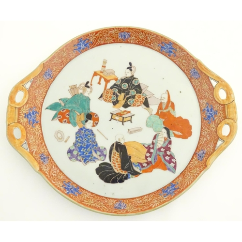 12 - A Japanese twin handled plate with hand painted decoration depicting six seated figures with scrolls...