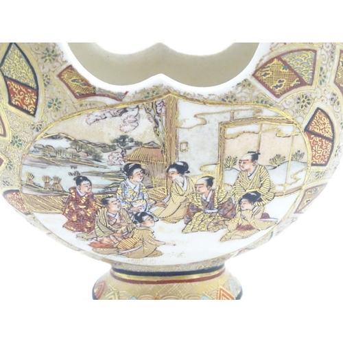 16A - A Japanese satsuma moon basket vase with hand painted decoration depicting figures seated around imp...