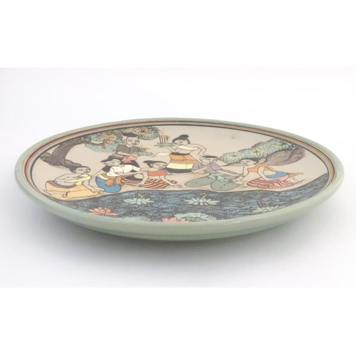 17 - An Oriental plate, the unglazed centre decorated with a group of people in a landscape relaxing near...