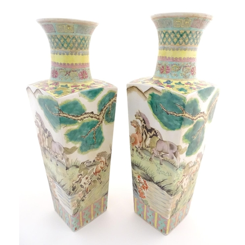 25 - A pair of Chinese square sectional vases with flared rims, decorated with horses in a landscape scen...