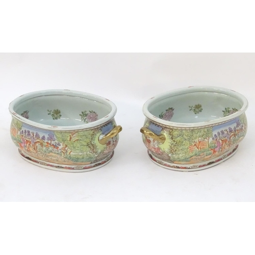 26 - A pair of Chinese foot baths, the exterior decorated with landscape hunting scenes with figures with...