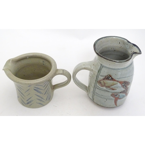 28 - Two studio pottery jugs, one with stylised fish decoration, the other with brushwork chevron detail....