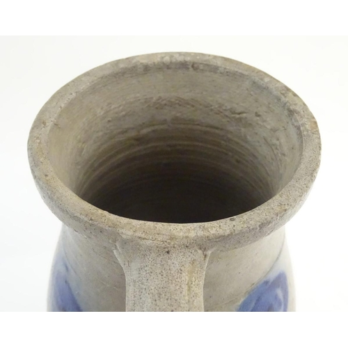 29 - A studio pottery vase with a single handle and stylised blue flower decoration. Incised 21 under han...