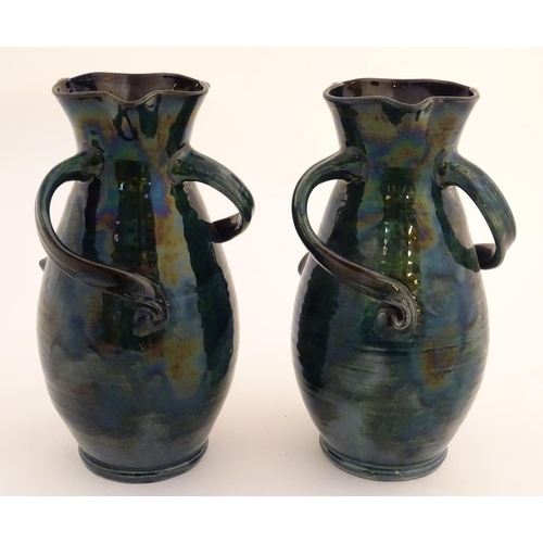 35 - A pair of Baron Barnstaple art nouveau vases in a lustre glaze, with lobed rims and three twisted ha...