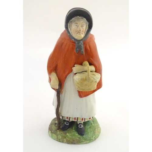 37A - An 18th / 19thC Staffordshire figure modelled as an old lady in a bonnet carrying basket. Approx. 7