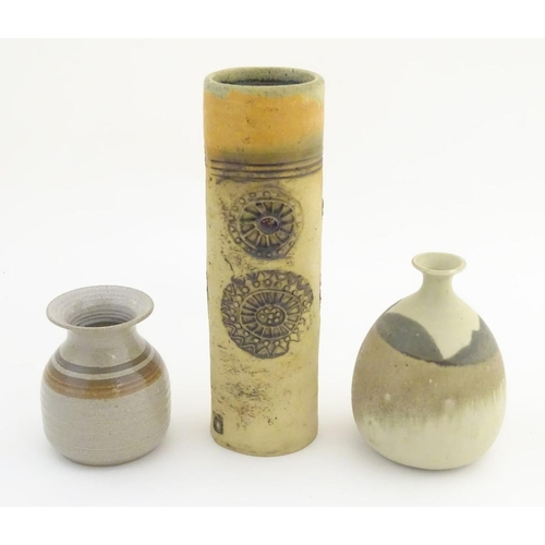 45 - Three studio pottery vases, a tall hand built vase with cut and incised roundel decoration, by Bob D...