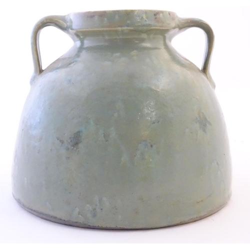 36 - A Brannam of Barnstaple twin handled squat vase with a mottled green glaze. Impressed C H Brannam Lt...