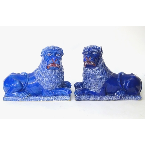 37 - A pair of 19thC faience Luneville lions with a cobalt blue glaze. Depicting recumbent lions on recta...
