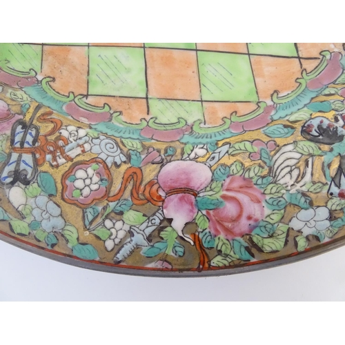 11 - Two oriental plates, one decorated with flowers, foliage and stylised birds. The other with a centra...