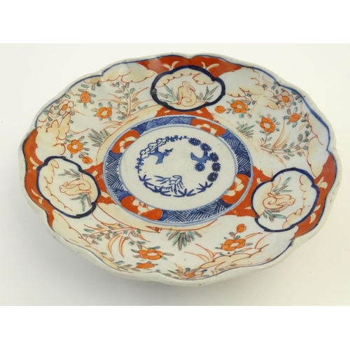 19 - An Imari style plate with a lobed rim, decorated with floral and foliate scenes with panelled depict...