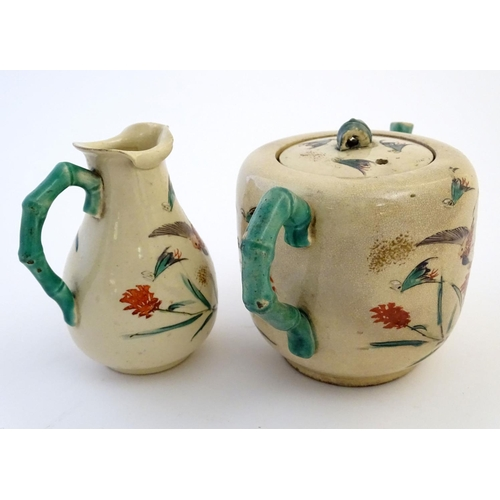 22 - A Japanese teapot and milk jug with hand painted decoration depicting birds and flowers, the handles...