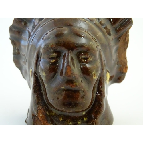 32 - A 19thC treacle and slip glazed terracotta window stop formed as the bust of Native American Indian ...