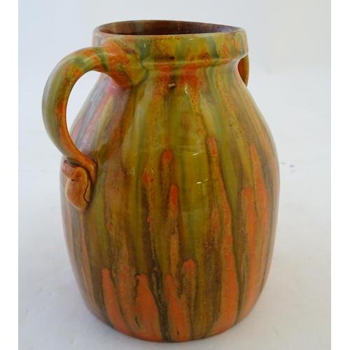 34 - A Brannam of Barnstaple twin handled Barum ware vase with and orange and ochre drip glaze, the handl...