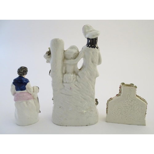 40 - Three items of Staffordshire pottery, to include a figural bud vase, a flatback house and a figure w...