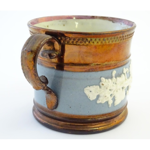 51 - A 19thC copper lustre mug with banded vine decoration in relief and pink lustre rim. Approx. 3 1/2