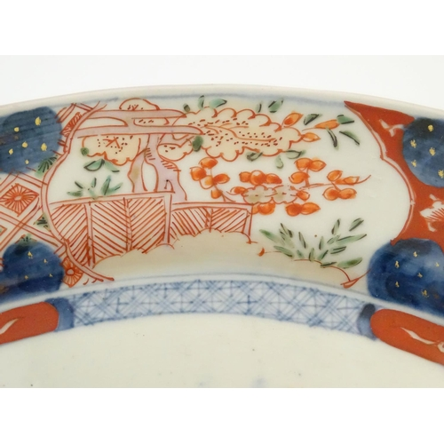 7 - A Japanese Imari style plate, the centre decorated with a vase of flowers with a floral border. Appr...