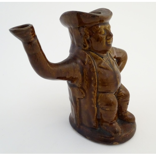 38A - A treacle glazed Toby jug teapot formed as a seated man, his arms forming the handle and spout. Appr...