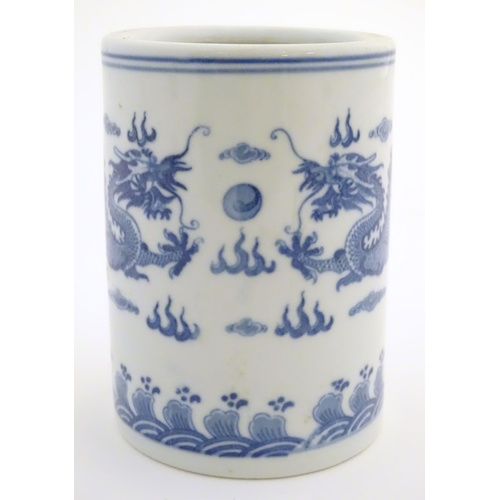 7 - A Chinese blue and white cylindrical brush pot decorated with stylised dragons, clouds and flames. C...