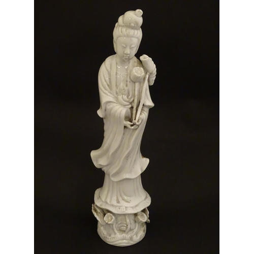 8 - A Chinese blanc de chine figure of Guanyin holding flowers, raised on a base of lotus flowers and li...