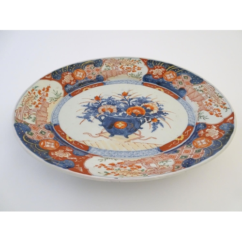 9 - A Japanese Imari style plate, the centre decorated with a vase of flowers with a floral border. Appr...