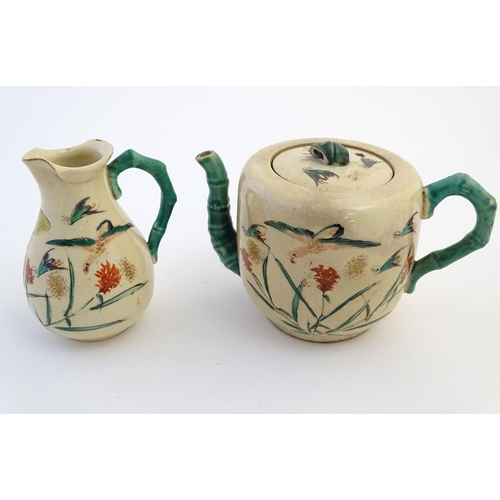 17 - A Japanese teapot and milk jug with hand painted decoration depicting birds and flowers, the handles...