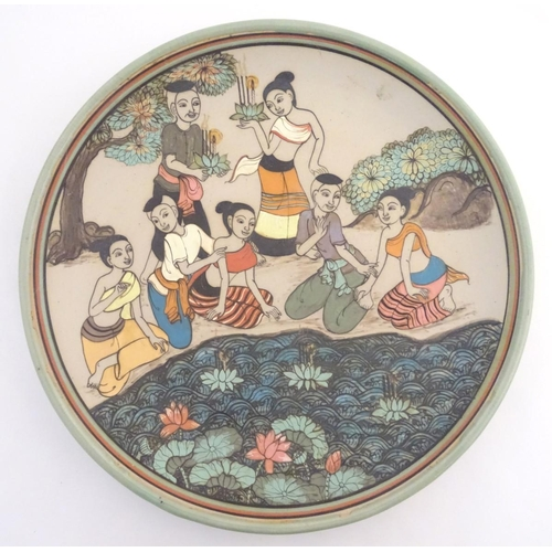 21 - An Oriental plate, the unglazed centre decorated with a group of people in a landscape relaxing near...