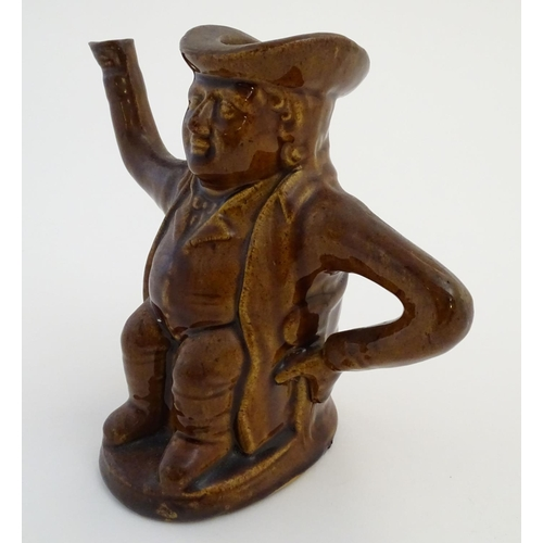 34 - A treacle glazed Toby jug teapot formed as a seated man, his arms forming the handle and spout. Appr...